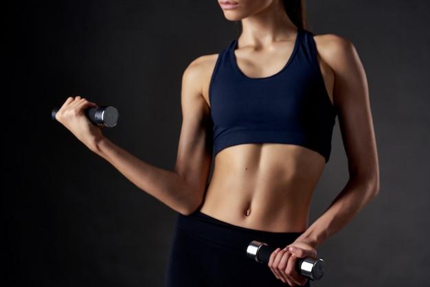 手にダンベルを持った女性が体を鍛えた体育館エクササイズフィットネス