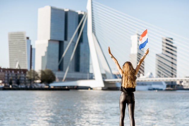 Woman with dutch flag enjoying beautiful cityscape view on the modern riverside during the morning in rotterdam city