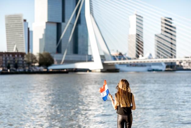 ロッテルダム市の朝の間にモダンな川沿いの美しい街並みの景色を楽しむオランダの旗を持つ女性