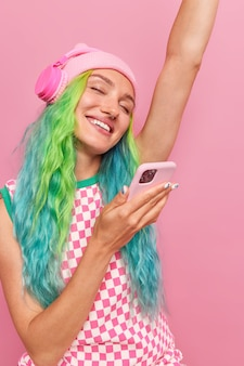 Woman with dyed colorful hair dances with arm raised up listens favorite music via headphones holds mobile phone isolated on pink