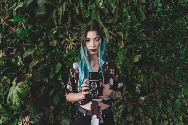 Woman with dyed hair holding retro styled camera in front of plant