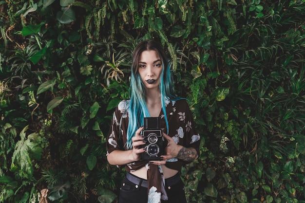 식물 앞에서 레트로 스타일의 카메라를 들고 염색 머리를 가진 여자