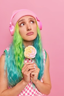 Woman with dyed hair holds delicious candy feels unhappy has melancholic expression listens music via headphones wears hat checkered dress isolated on pink