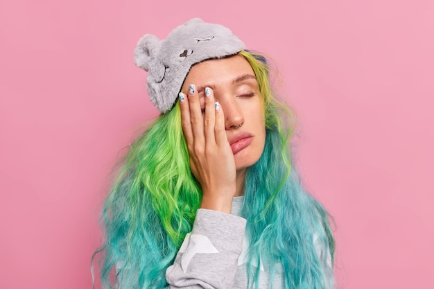 Woman with dyed hair keeps hand on face closes eyes feels onworked after sleepless night wears slumber suit blindfold on forehead poses on pink