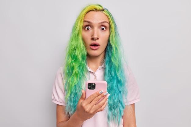 염색한 옷을 입은 여성은 휴대전화에서 예상치 못한 알림을 받습니다. 회색으로 격리된 티셔츠를 입은 모바일 제안에 그녀의 눈이 감정적으로 반응한다는 것을 믿을 수 없습니다