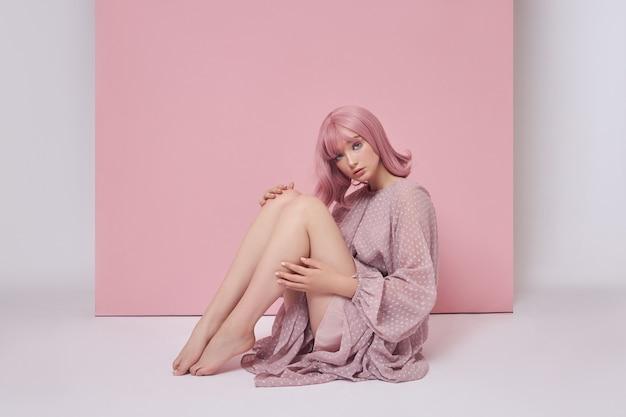 ピンクに染めた髪のロングドレスを着た女性が床に座っている。ピンクの壁に髪を染めた少女のポートレート。完璧なヘアスタイルとヘアスタイル