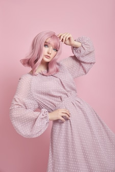 Женщина с крашеными розовыми волосами в длинном платье. портрет девушки с окраской волос у розовой стены
