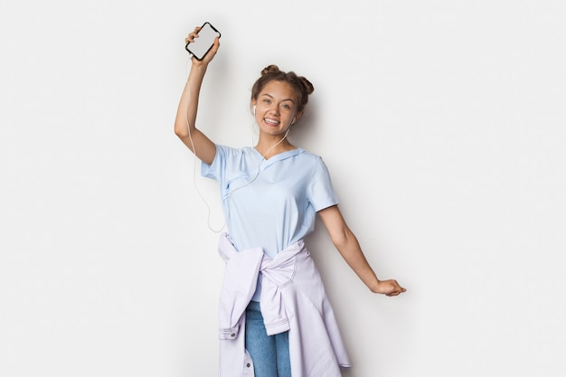 Woman with earphones is showing at camera her phone screen