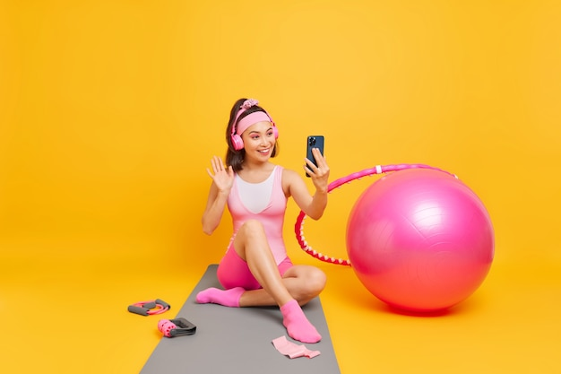 東部の外観を持つ女性がスマートフォンのカメラでこんにちは波を持っていますビデオ通話を使用していますワイヤレスヘッドフォンを使用して黄色で隔離されたカレマットに座っています
