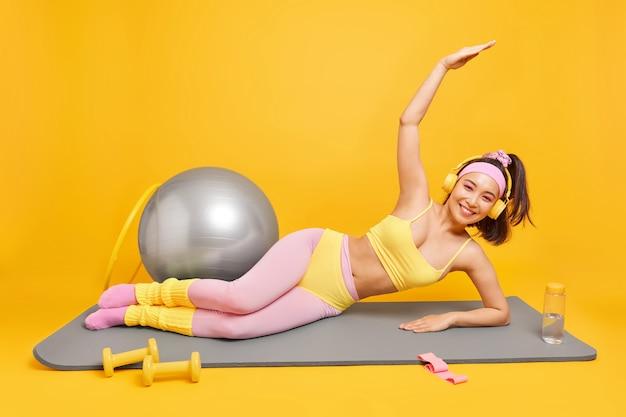 Женщина с восточной внешностью лежит на коврике для фитнеса, делает боковую планку, держит руку поднятой, слушает музыку через наушники, одетая в спортивную одежду, поддерживает форму, использует спортивное оборудование.