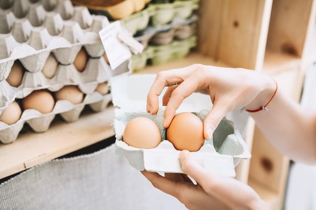 ゼロウェイストショップで地元の農場からバイオ有機卵を購入する卵パックボックスを持つ女性