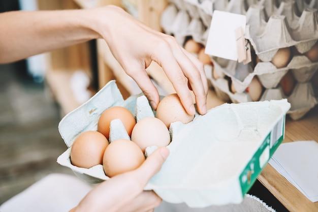 제로 폐기물 가게에 있는 지역 농장에서 유기농 계란을 사는 계란 상자를 든 여성