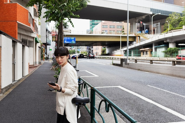 스마트 폰을 사용하는 도시에서 전기 자전거를 가진 여자
