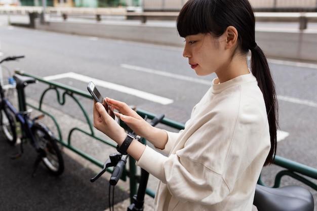 Женщина с электрическим велосипедом в городе с помощью смартфона
