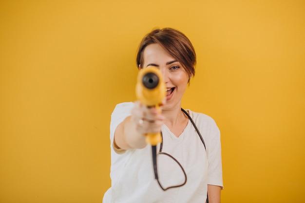 Donna con trapano elettrico su sfondo giallo