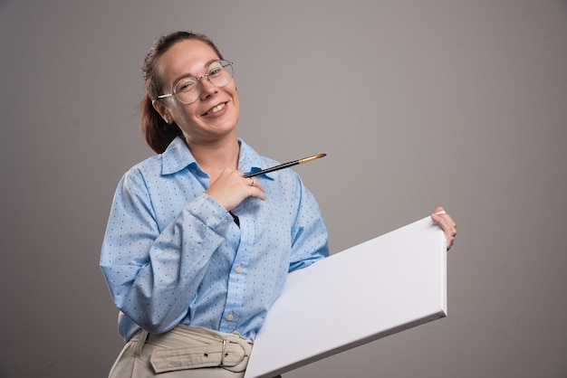 Woman with empty canvas and brush on gray background