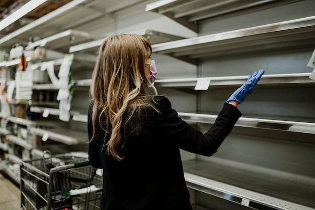 코로나바이러스 전염병 동안 슈퍼마켓에 빈 선반이 있는 여성