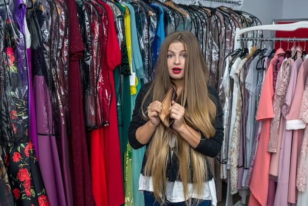 Женщина с пустым кошельком в магазине платьев
