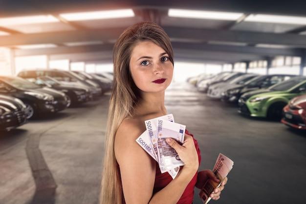 車を買うガレージでユーロ紙幣を持つ女性