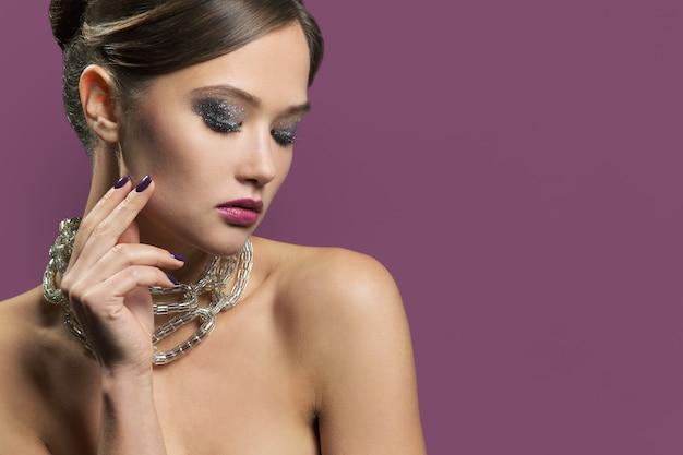 Женщина с вечерним макияжем и обнаженными плечами