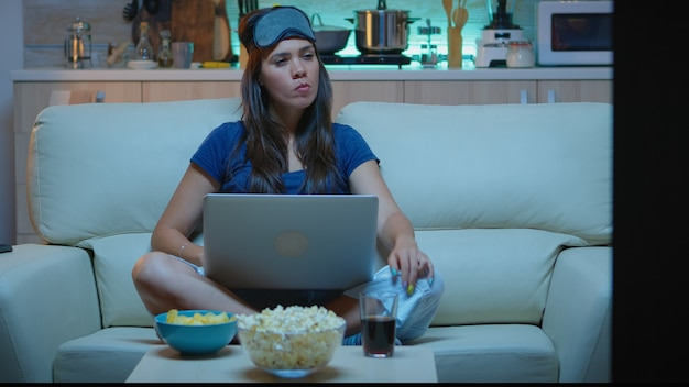 Woman with eye mask using laptop at night while watching tv and eating snacks. happy person in pijamas sitting on sofa reading writing searching browsing on notebook using internet checking mails