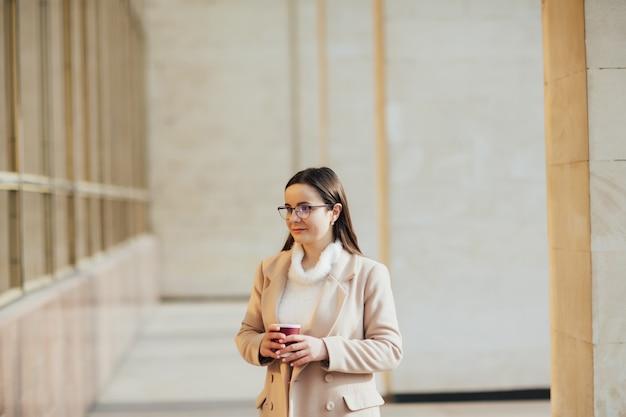 眼鏡をかけた女性が休憩中にオフィスビルの近くでコーヒーを飲んでいます Premium写真