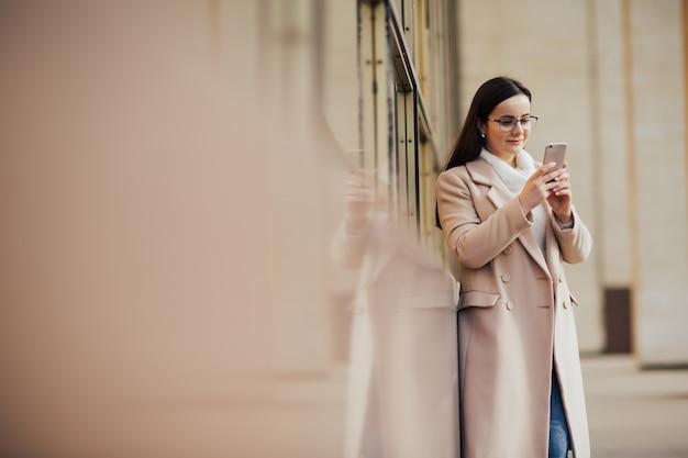 眼鏡をかけた女性が市内でスマートフォンを使用しています