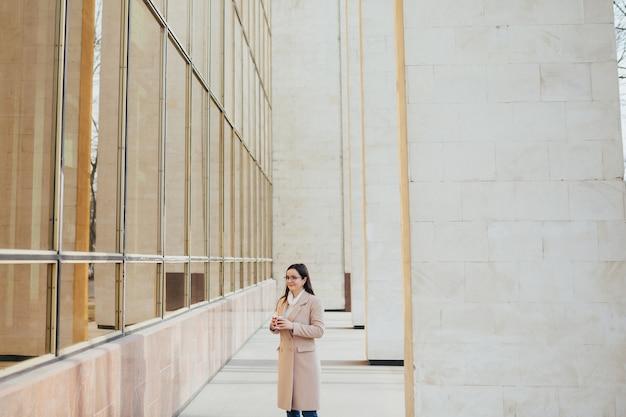 パノラマの窓とオフィスの近くの眼鏡を持つ女性は休憩時にコーヒーを飲む
