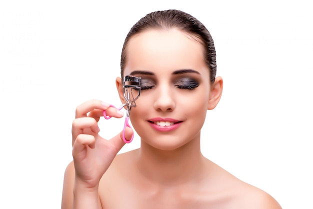 Woman with eyelash curler isolated on white