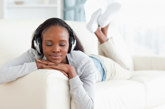 Woman with eyes closed enjoying music on her couch