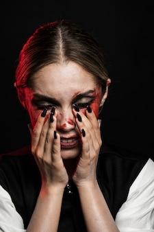 Donna con gli occhi chiusi e sangue finto