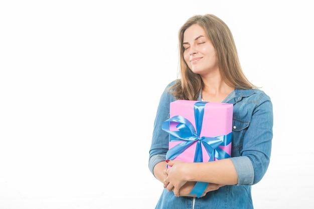 白い背景に誕生日の贈り物を保持している目を閉じた女性