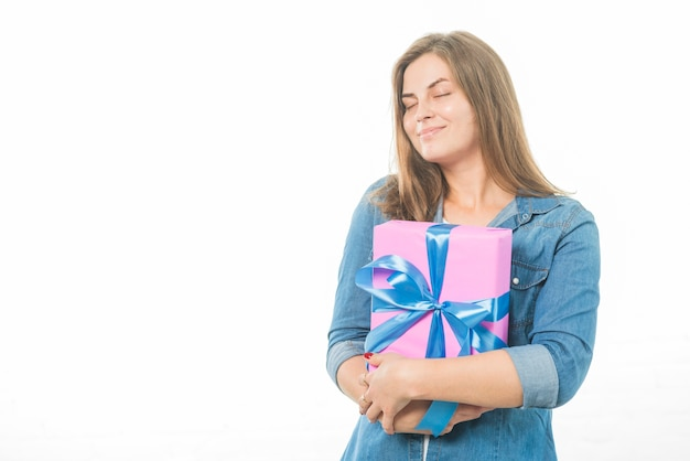 Woman with eyes closed holding birthday gift on white background