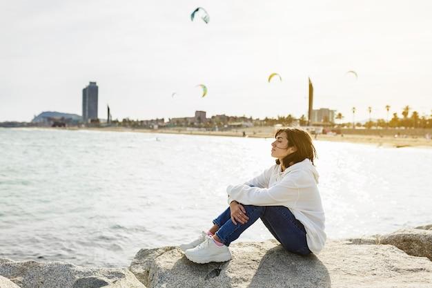 Женщина с закрытыми глазами сидит на камне, наслаждаясь свежим бризом и солнечным светом