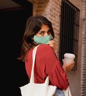コーヒーのカップを保持している屋外でフェイスマスクと食料品の袋を持つ女性