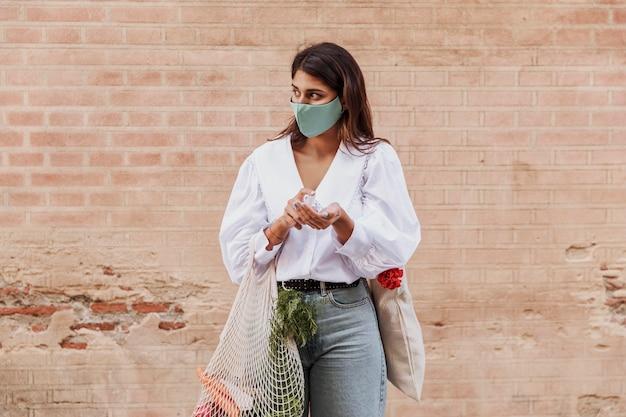 Женщина с маской для лица и продуктовыми пакетами, использующая дезинфицирующее средство для рук