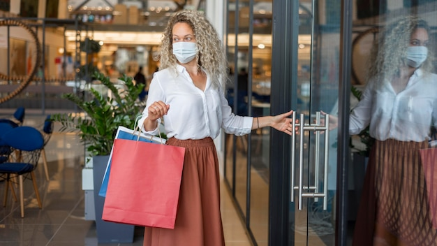 Woman with face mask carrying shopping bags