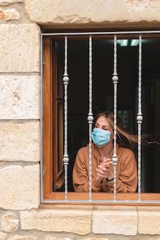 ウィンドウで拍手フェイスマスクを持つ女性