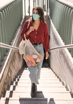 Woman with face mask climbing stairs while holding grocery bags