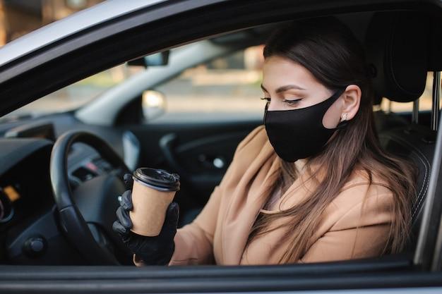 コロナウイルスのパンデミック中にコーヒーを飲みながら車を運転しているフェイスマスクの女性、