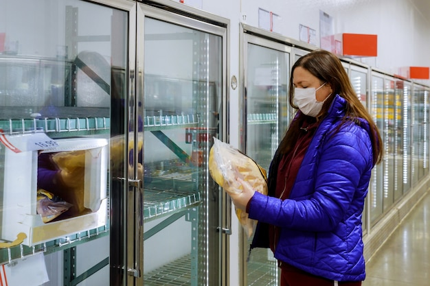 Woman with face mask holding bag of frozen chicken at supermarket with empty shelves.