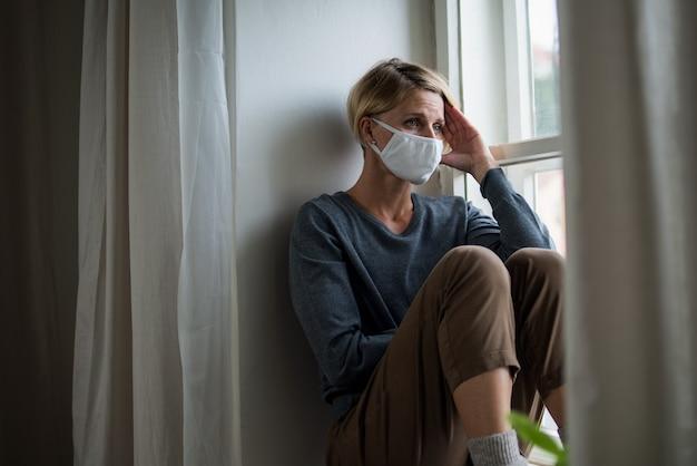 집에서 안면 마스크를 쓴 여성은 스트레스, 정신 건강, 코로나바이러스 개념을 느끼고 있습니다.