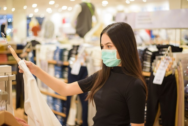 フェイスマスクを持つ女性はショッピングセンターで服を買い物