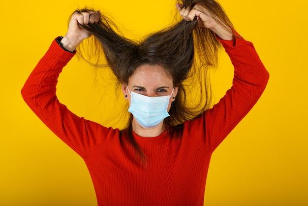 마스크를 쓴 여성은 코로나 19 바이러스로 피곤하고 스트레스를받습니다. 노란색 배경