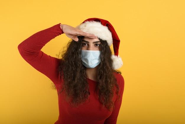 フェイスマスクをした女性は何かを遠くに探します。