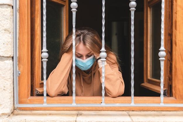 窓の外を見てマスクを持つ女性