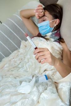 Covid19의 아픈 소파에 누워 얼굴 마스크를 가진 여자.