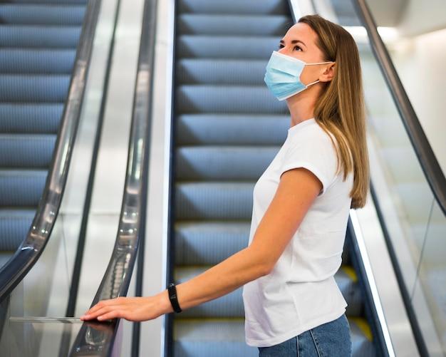 エスカレーターでフェイスマスクを持つ女性