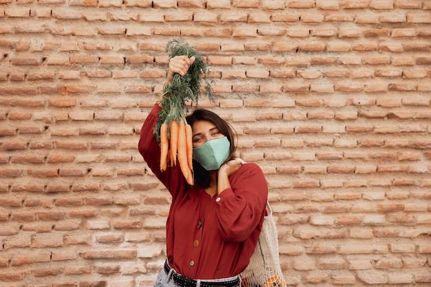 Женщина с маской для лица на открытом воздухе держит морковь