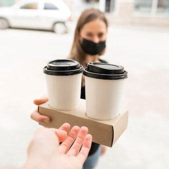 Woman with face mask receiving take away coffees